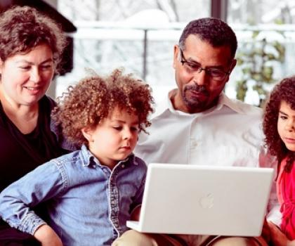 Family around laptop - Expanding the Impact of Music Education Digitally
