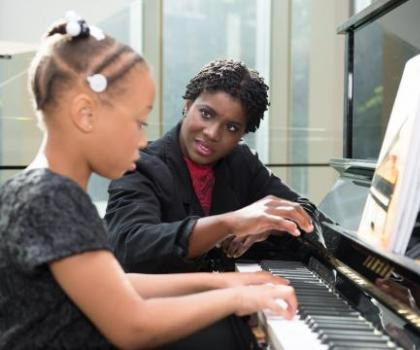 elementary student and teacher learning at the piano
