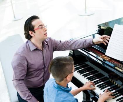 intermediate student and teacher learning at the piano