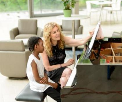 woman teaching young student at piano