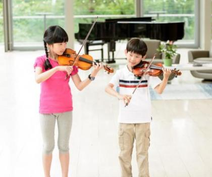 two violin students perform a duet